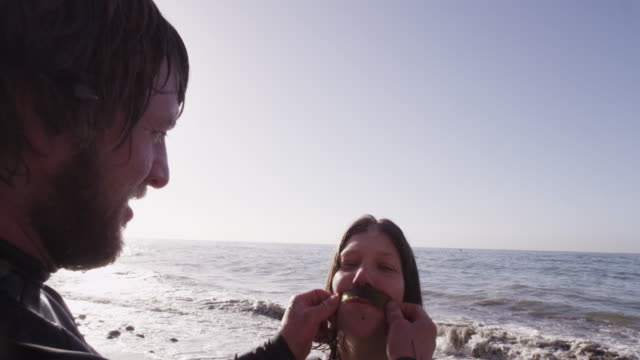 Man puts seaweed mustache on woman, slow motion