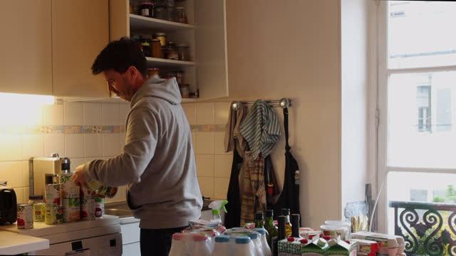 vidéos et rushes de a man puts the groceries in a cupboard - organisation