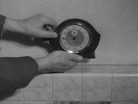 A man puts the hands on a mantel clock back by an hour