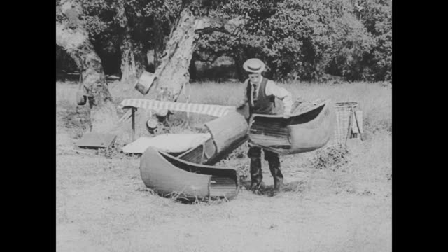 vídeos de stock, filmes e b-roll de 1923 man (buster keaton) puts together a canoe and goes fishing - 1923