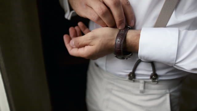 man puts wrist watch on his hand - suspenders stock videos and b-roll footage