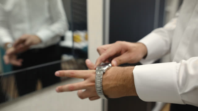 man puts wrist watch on his hand while standing in front of a mirror - millionnaire stock videos & royalty-free footage
