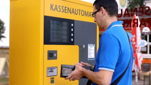 vídeos y material grabado en eventos de stock de hombre poner un carro en un estacionamiento pago de máquina - aparcamiento