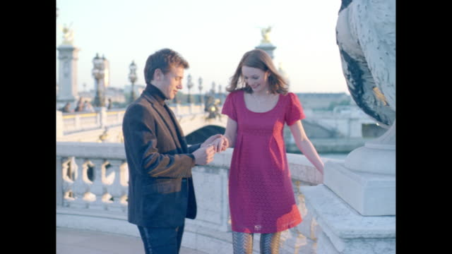 Man putting a ring on a woman's finger in Paris.
