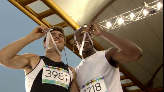 vidéos et rushes de la ms man putting arms up and blowing kisses to stadium after winning medal in track event/ second winner joining man up on riser to show off medals/ sheffield, england - médaille récompense