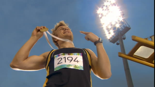 la ms man putting arms up and blowing kisses to stadium after winning medal in track event/ man bending over to shake hands with someone before kissing his medal/ sheffield, england - medaglia premio video stock e b–roll
