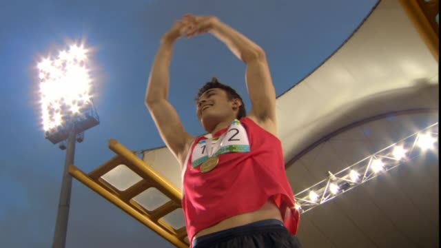 LA MS Man putting arms up and waving to stadium after winning medal in track event/ Sheffield, England