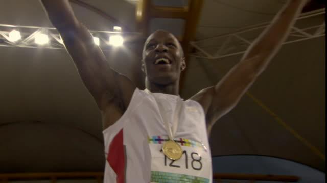 vídeos de stock, filmes e b-roll de la ms man putting arms up and waving to stadium after winning medal in track event/ sheffield, england - atleta de campo e pista