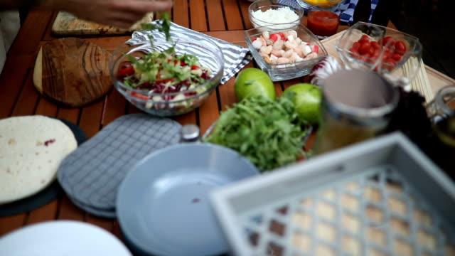 Man putting arugula in salad