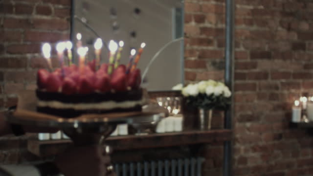 CU MS SLO MO Man putting birthday cake on dining table, guests clapping and toasting wine / New York City, New York, USA