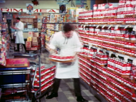 1965 man putting carton of canned soup on shelf of grocery store / educational - tin stock videos & royalty-free footage