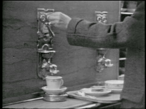 vídeos de stock, filmes e b-roll de b/w 1957 man putting coin in + turning spigot of automatic coffee dispenser - 1957