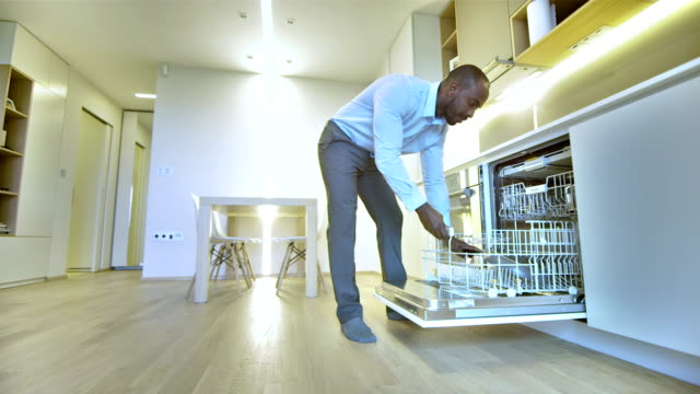 ls man putting dishes into a dishwasher - dishwasher stock videos & royalty-free footage