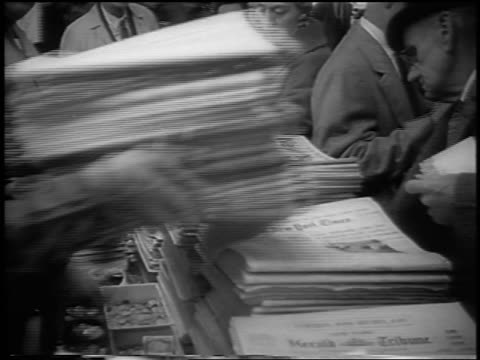 vidéos et rushes de b/w 1963 man putting down stack of newspapers as people buy them at newsstand / nyc - kiosque à journaux
