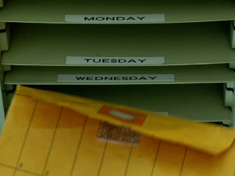 CU, Man putting envelope into filing tray, close-up of hand