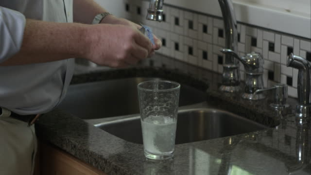 Man putting eporvesant tablets in a glass of water, then drinking it.