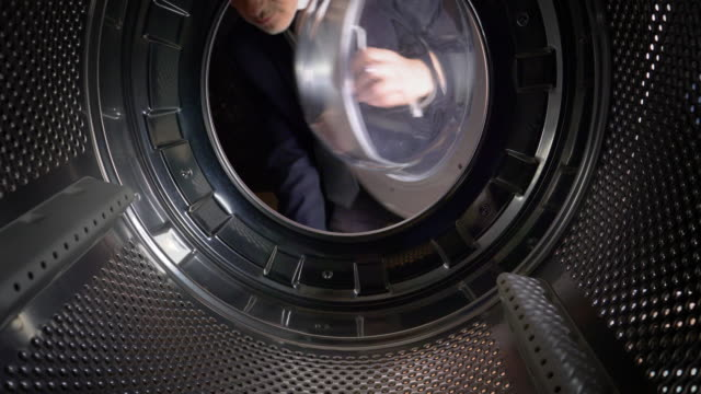 pov man putting euros into a washing machine - laundry stock videos & royalty-free footage