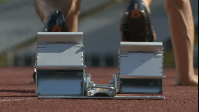 cu man putting feet on starting block and crouching in starting position on sports track/ sheffield, england - アシ点の映像素材/bロール