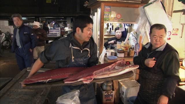 ms man putting fish on counter, tsukiji fish market, tokyo, japan - ファーマーズマーケット点の映像素材/bロール