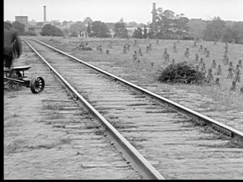 stockvideo's en b-roll-footage met 1915 b/w ws man putting handcar on railroad and pumps away - 1915