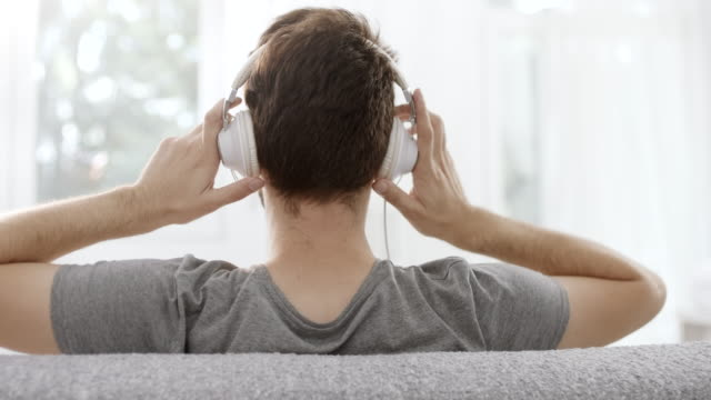 man putting headphones on his ears - riposarsi video stock e b–roll