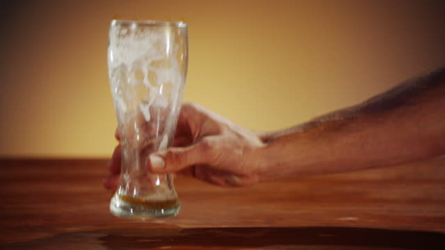 vídeos de stock e filmes b-roll de homem colocando o vazio de cerveja no bar balcão - copo vazio