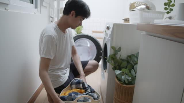 man putting laundry into washing machine - hamper stock videos & royalty-free footage