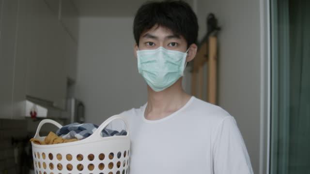 vídeos de stock, filmes e b-roll de homem colocando roupa na máquina de lavar - lavanderia edifício público