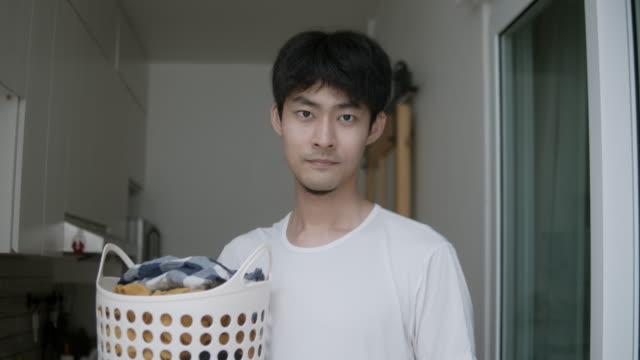 洗濯物を洗濯機に入れる男 - 洗濯かご点の映像素材/bロール