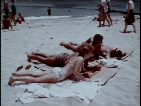 man putting lotion on a woman's back / couples lying on towels on a beach - sun cream stock videos & royalty-free footage