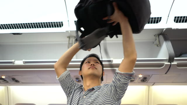 Man putting luggage on the top shelf on airplane, Travel