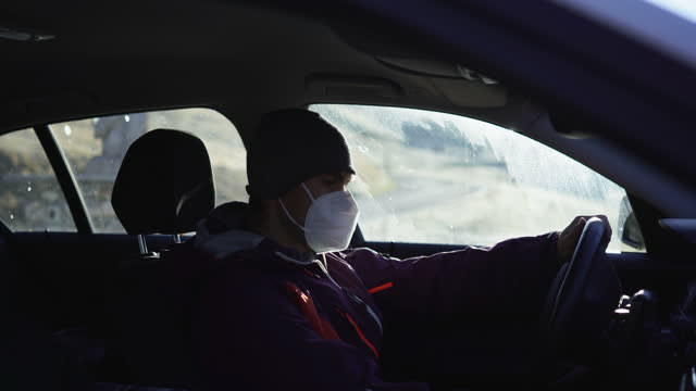 man putting on a health mask in a car on a mountain pass in switzerland - warm clothing stock videos & royalty-free footage