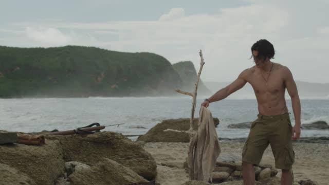 Man putting on a shirt by the shore