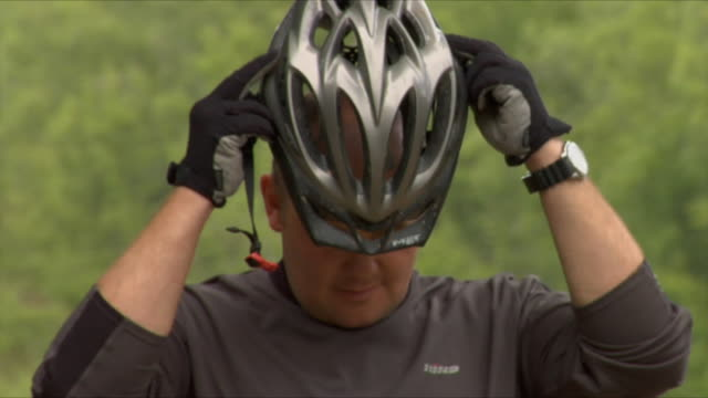 ms zi cu man putting on bike helmet and looking around in bedgebury forest / kent, england, uk - cycling helmet stock videos & royalty-free footage