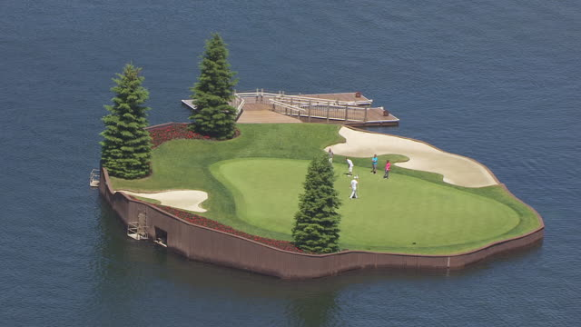 cu aerial zo man putting on floating green with golf course at coeur d'alene resort / coeur d'alene, idaho, united states - golfplatz green stock-videos und b-roll-filmmaterial