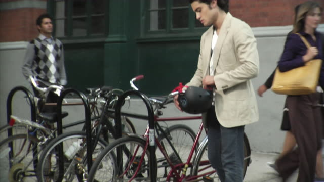 vídeos de stock e filmes b-roll de ms man putting on helmet and getting bike from rack, tribeca, new york, usa - capacete