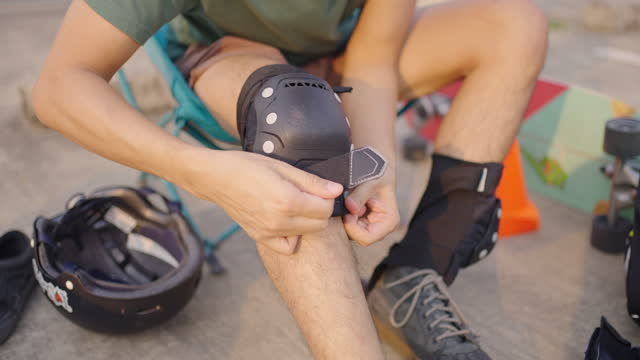 man putting on knee guard for safety before skateboarding. - sports helmet stock videos & royalty-free footage