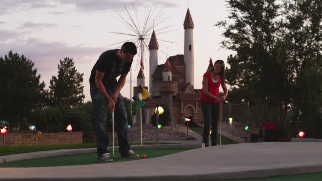 ws man putting on miniature golf course, woman watching standing nearby / orem, utah, usa - minigolf stock-videos und b-roll-filmmaterial