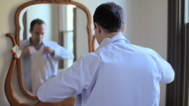 Man putting on shirt in front of mirror
