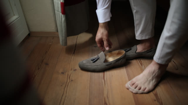 stockvideo's en b-roll-footage met man putting op schoenen - herenkleding