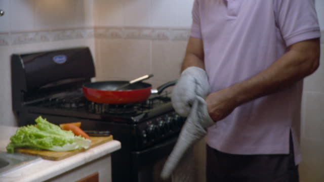 cu tu td man putting oven gloves and taking dish out of oven / havana, cuba - oven mitt stock videos and b-roll footage