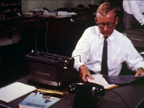 1960 man putting papers with carbon between into typewriter + starts typing at desk in office / doc. - journalism stock videos & royalty-free footage