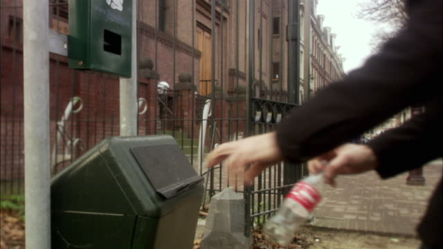 ms man putting plastic bottle in dustbin / rotterdam, netherlands - lanciare video stock e b–roll