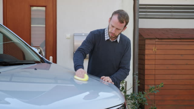 man putting polishing paste onto the hood of his silver car - television advertisement stock videos & royalty-free footage