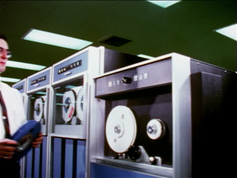 vídeos de stock, filmes e b-roll de 1965 man putting reel on tape drive in computer room / documentary - 1965