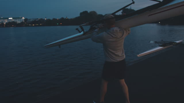 man putting rowboat in river at night - carrying stock videos & royalty-free footage