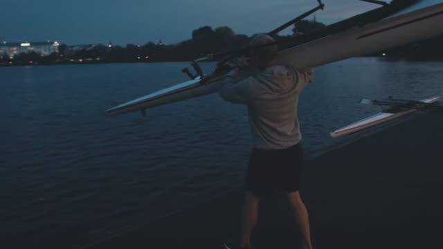 mann setzt ruderboot in fluss in der nacht - ruderboot stock-videos und b-roll-filmmaterial