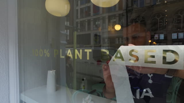 man putting sticker on window of meatfree neat burger fastfood joint in london uk on monday sept 2 2019 - sticker stock videos and b-roll footage