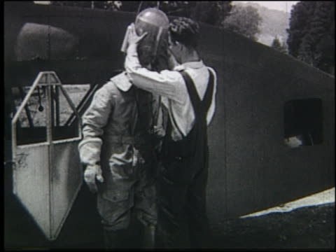 b/w man putting strange helmet on another man near flying contraption - air vehicle stock videos & royalty-free footage