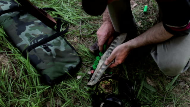 man putting the fired shotgun shells at the bandolier after shoot out - bandolier stock videos & royalty-free footage
